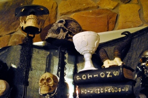 Spell books and skulls on the fireplace mantel.