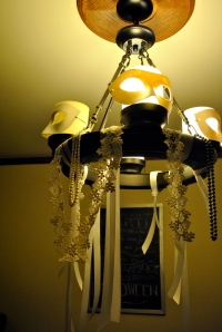 I dressed up the kitchen chandelier with masks, ribbons, lace, and beads.