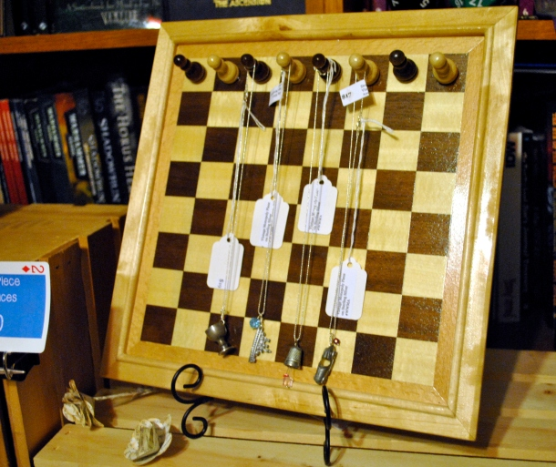 Wood chess board turned into a necklace display for game piece necklaces.