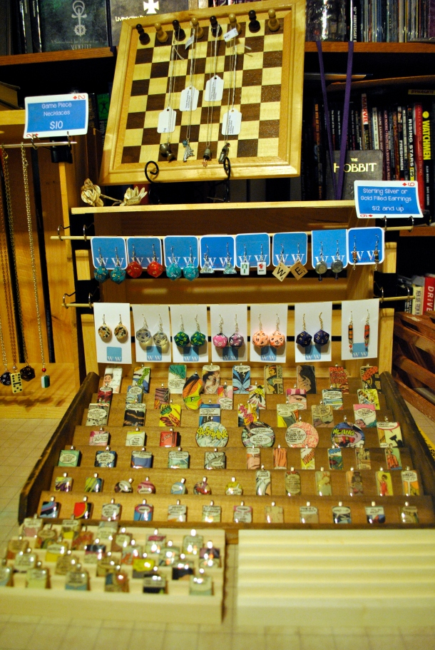 Comic pendants are displayed on an old printing block tray and domino stands. Behind them, earring cards hang from small dowels.